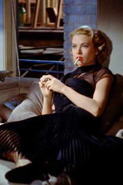 "Grace Kelly as Lisa Carol Fremont wearing a see-through black dress and smoking a cigarette on James Stewart aka L.B. ""Jeff"" Jefferies's sofa. 